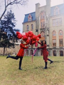 Two women pose with several Red and pink balloons On Penn's college Green