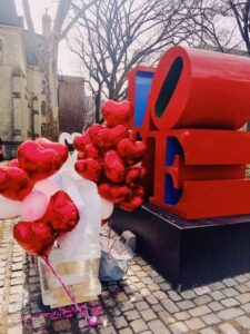dozens of red heart shaped balloons around a loveseat sculpted from ice, in front of Penn's Love statue