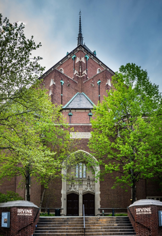 Exterior shot of Irvine Auditorium showing its red brick facade and church-like steeple. The building is framed by two lush green trees.
